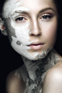 Beautiful girl with mud on his face. Cosmetic mask. Beauty face. Picture taken in the studio on a black background.